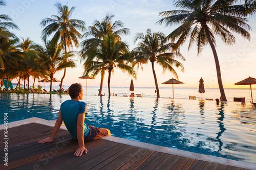 happy holidays in beautiful beach hotel at sunset, man sitting near swimming poo Wallpaper Mural