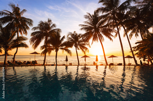 Wall Murals Bali beautiful sunset on the beach, holidays background, reflection of silhouettes of palm trees in swimming pool of hotel