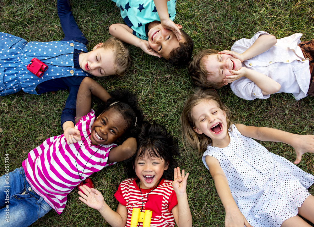 Fototapety, obrazy: Group of kindergarten kids lying on the grass at park and relax with smiling