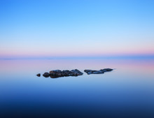 Tranquil Minimalist Landscape  With Rocks In Calm Water.