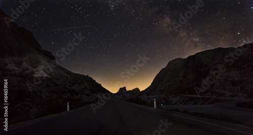 Fototapeta Starry night sky with the Milky Way over a mountain road