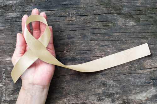 Cream awareness ribbon on helping hand support symbolic bow color for Degenerati Wallpaper Mural