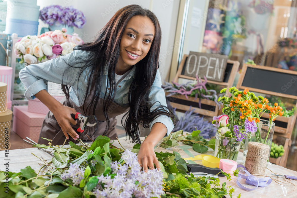 Fototapeta beautiful african american woman in apron holding secateurs while cutting flowers and smiling at camera in flower shop