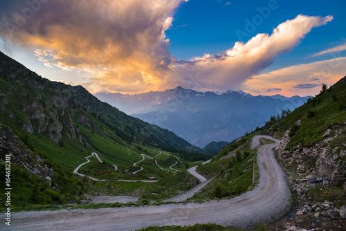 Zdjęcie XXL Brud góra droga prowadząca do przełęczy w Włochy (Colle delle Finestre). Wydający widok na zachód słońca, kolorowe dramatyczne niebo, przygody w okresie letnim, włoskie Alpy.