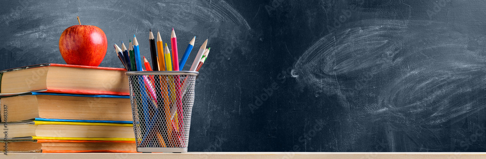 Fototapeta Back to School. Accessories, books and fresh apple against chalkboard