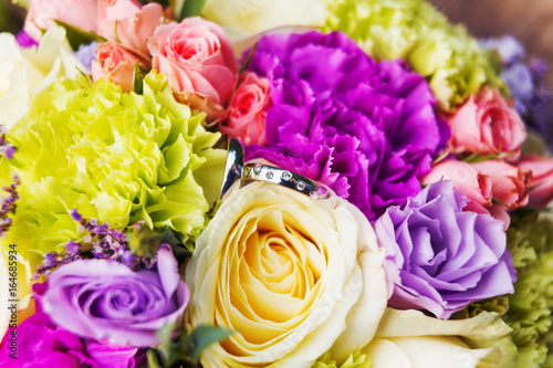 Golden wedding rings with diamonds lie inside rose flower in the bridal bouquet. Symbol of love and marriage. © Konstantin Aksenov