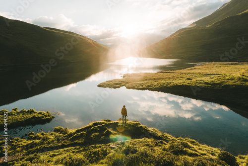 Poster Muziekwinkel Young male standing in front of a warm summer sunrise reflection of the sky at a mountain lake.