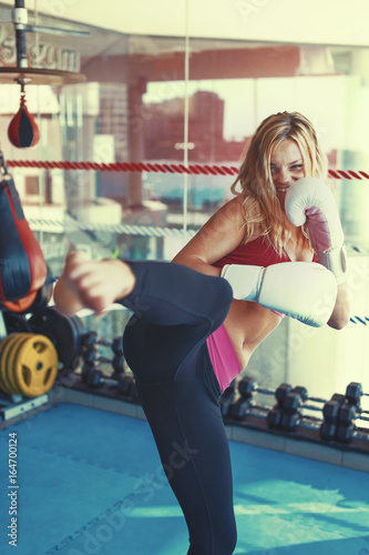 Young martial artist woman kicking in gym into camera graded Canvas Print