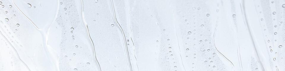 Fensterscheibe mit abperlendem Wasser als Hintergrund
