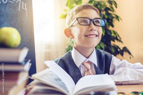 Zdjęcie XXL Powrót do szkoły. Śliczny dziecka obsiadanie przy biurkiem w sala lekcyjnej. Chłopiec ostrożnie siada na lekcji