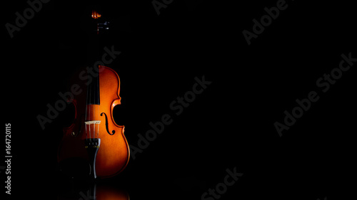 Isolated classical violin against a black background. Low key image. Empty copy space for Editor's text. - 164720115