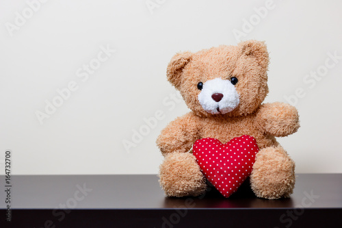 bear doll and red heart on wooden table #164732700