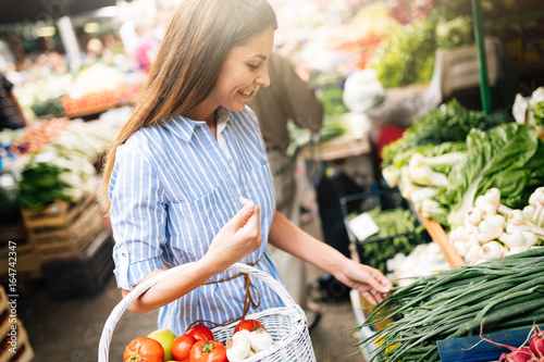 Fotografía  Picture of woman at marketplace buying vegetables