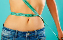 Woman Measuring Her Waist Over Blue Background. Wellness Concept.
