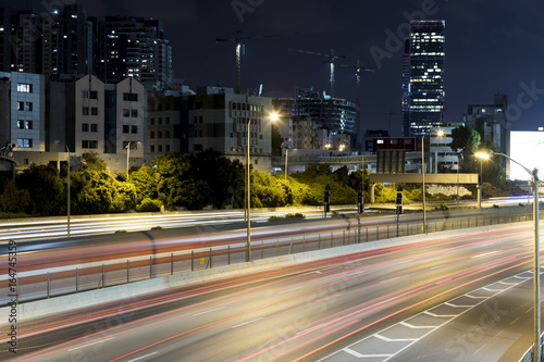 Photographie  Long exposure of highway with car lights buildings on background and lighted cra