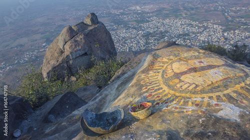 A stone with the image of the footprints of a guru on top of a mountain Arunachala.