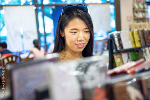 Photo Stands Music store Asian girl buying a compact disc
