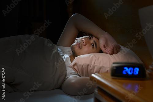 Obraz Depressed man suffering from insomnia lying in bed - fototapety do salonu