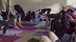 Medium slow motion panning shot of yoga class changing poses / Provo, Utah, United States