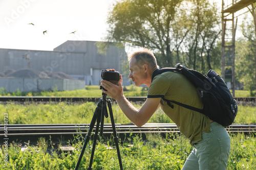 Obraz na plátne A man is filming outdoor.