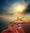 Woman walking on Dead Sea salt shore towards the sun