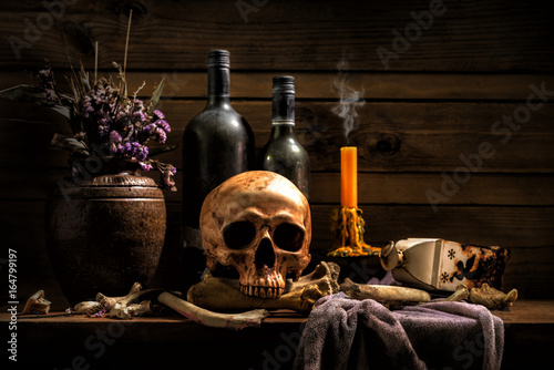 Fotografía  Still Life Skull , Bone ,Wine Bottles , Candle Light , on Old Wood Table Backgro
