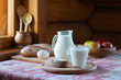 Village breakfast. A glass of milk, bread and fruit are on the table near the window in the rustic house.