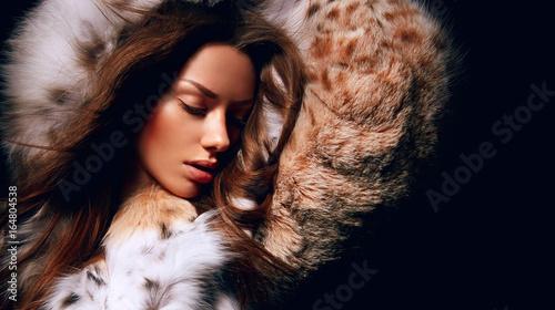 Foto Luxury girl with long brown hair in a fur coat