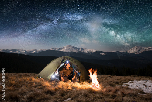 Poster Camping Male tourist have a rest in his camping in the mountains at night. Man with a headlamp sitting near campfire and tent under beautiful night sky full of stars and milky way, and enjoying night scene