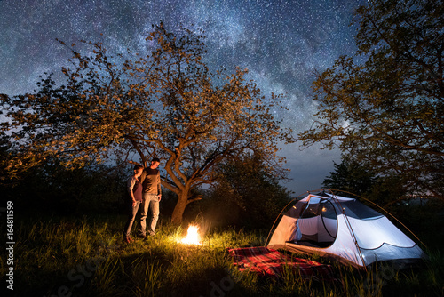 Fototapeta Romantic pair tourists standing at a campfire near tent under trees and beautiful night sky full of stars and milky way. Night camping. Astrophotography obraz na płótnie