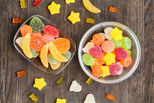 Poster Confiserie Bowls with delicious jelly candies on wooden background