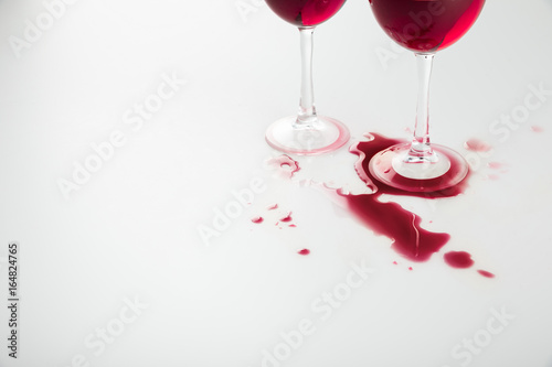 close-up view of wineglasses with red wine and wine spilled isolated on white Fototapeta