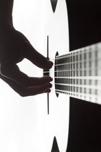 Man' S Hand Playing On Classical Guitar Against A Background Of Daylight
