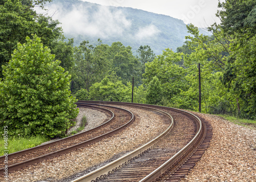 Railroad Curving Double Railroad Tracks through Foggy Mountains
