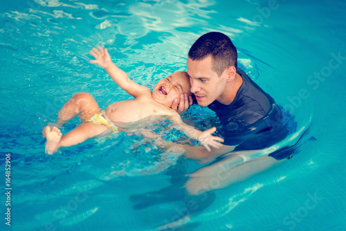 Swimming instructor with cheerful baby boy on swimming class