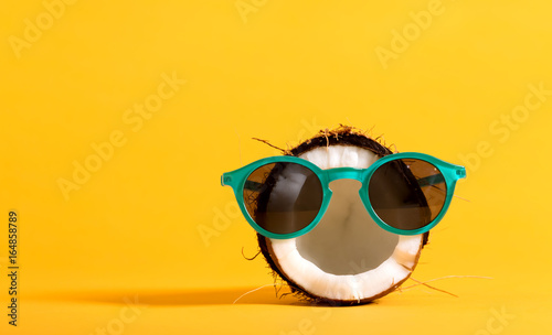 Obraz na plátne Fresh coconut wearing sunglasses on a bright yellow background