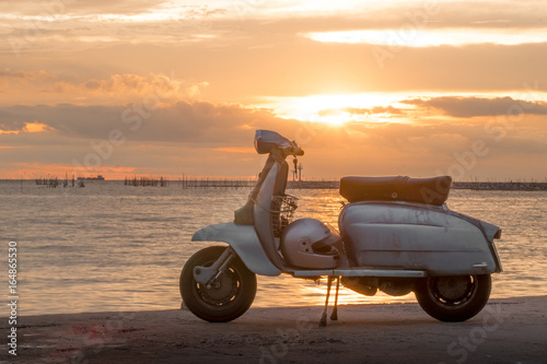 Scooter The joy of travel rider Concept . Happy traveling on motorcycle scooter on bridge at the sea during his time at sunset - An impressive collection of romantic memories.