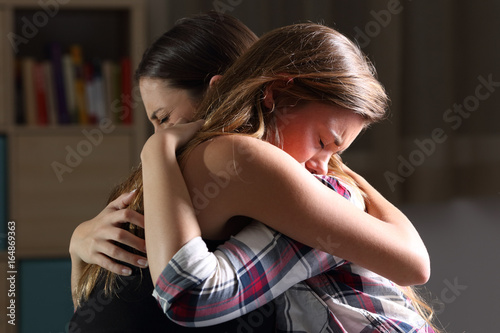Two sad teens embracing at bedroom Canvas Print