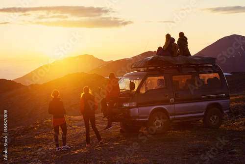 Travel concept with friends, sunset and car