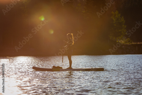 фотографія  Paddle boarding at sunrise on a mountain lake