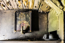 A Sacred Heart Picture Of Jesus Hangs On The Wall Of A Very Dirty House With Peeling Paint