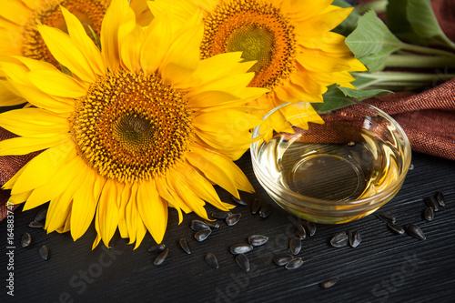 Fototapeta Sunflower oil with seeds and sunflowers on black background obraz