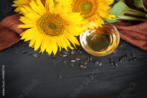 Fototapeta Sunflower oil and sunflowers with copy space on black background obraz