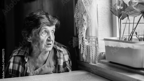 Elderly woman grieves near the window genre photography in black and white