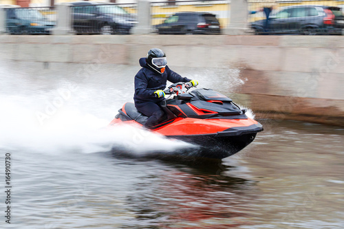 Keuken foto achterwand Water Motor sporten Young guy cruising on the a river chanel on a jet ski