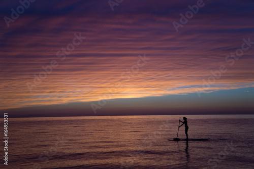 Beautiful lake sunset with woman on paddle board.