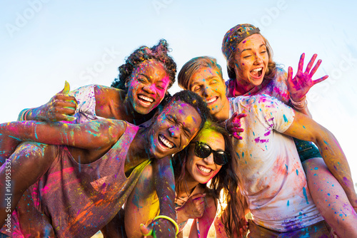 Obraz happy young multiethnic friends with colorful paint on clothes having fun together at holi festival - fototapety do salonu