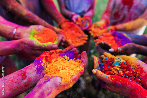 close-up partial view of young people holding colorful powder in hands at holi f Плакат