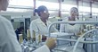 Slowmo of three female engineers in lab coats and protective eyeglasses discussing something in industrial factory