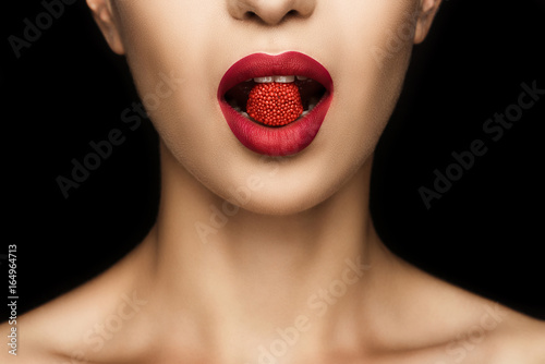 cropped view of sensual woman with red jelly candy in mouth, isolated on black